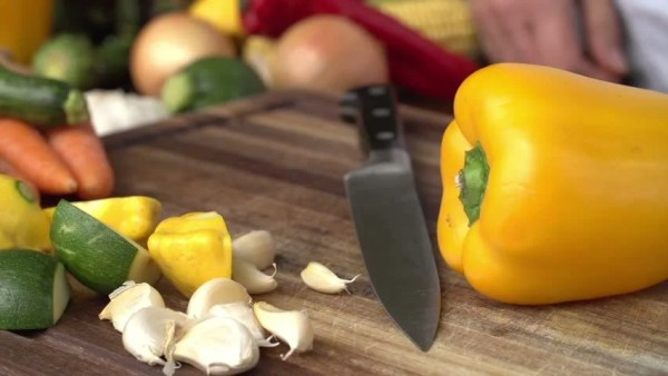 Cook Cutting Garlic On A Chopping Board Stock Footage