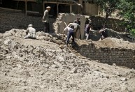 Men digging to recover building materials from houses newly buried by a mud flow
