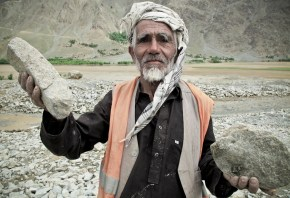 A man selects stones from a debris flow area, to be sold as building material once back in the city