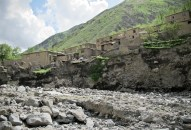 A village threatened by severe erosion undercutting the slope.