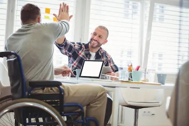 Male client in wheelchair and male caseworker sitting at desk, doing 'high-five.' Smiling.