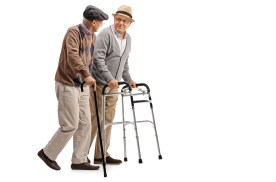 Two senior men walking together, talking, one using a cane and the other a walker.