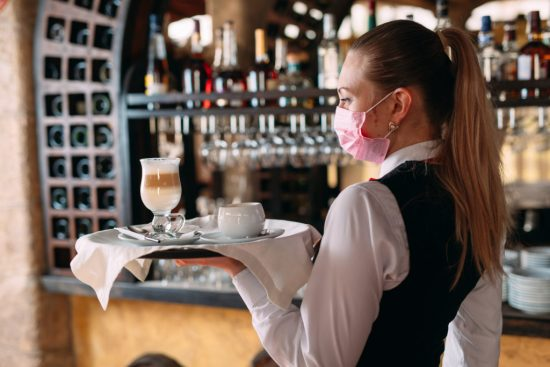 A female Waiter of European appearance in a medical mask serves Latte coffee.