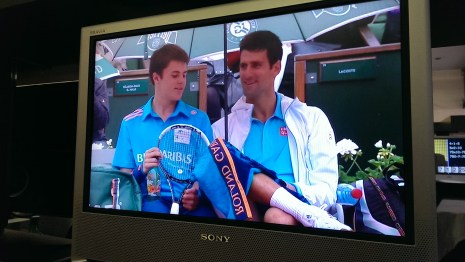 Djokovic sharing a funny moment with a ballboy during a rain break