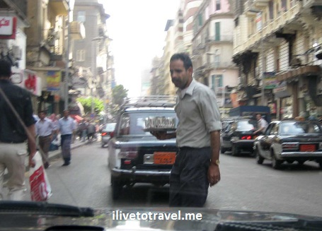 Tea server crossing street in Cairo with a tray full of tea