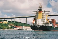 Cargo ship entering St. Anna Bay with the Queen Juliana bridge in the background in Willemstad, Curacao