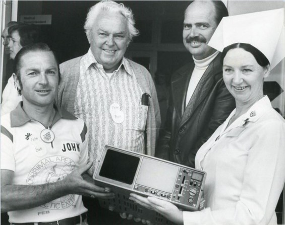 P25830 - Syd Atkins (second from left) with medical and nursing staff receiving medical donation from Corrimal Apex Club, 9 March 1983
