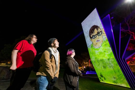 Participants View Light Projections of Mural Artworks