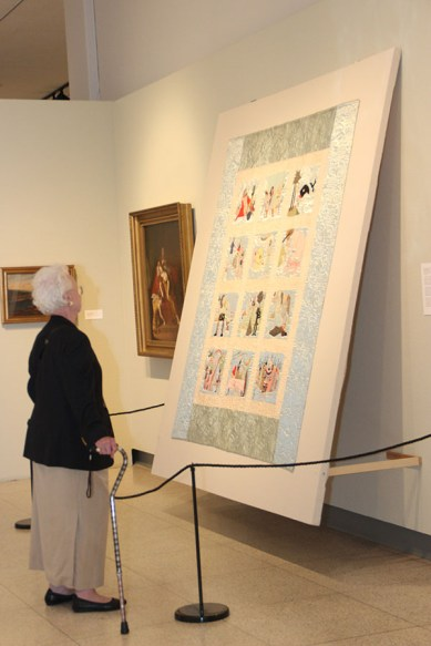 Visitor views a quilt in the Spectrum art exhibition.