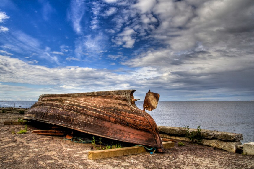 Rusty boat lying on girders on shore with light cloudy ocean background