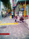 This little miss was following her mother while diligently pushing her own pram. :)
