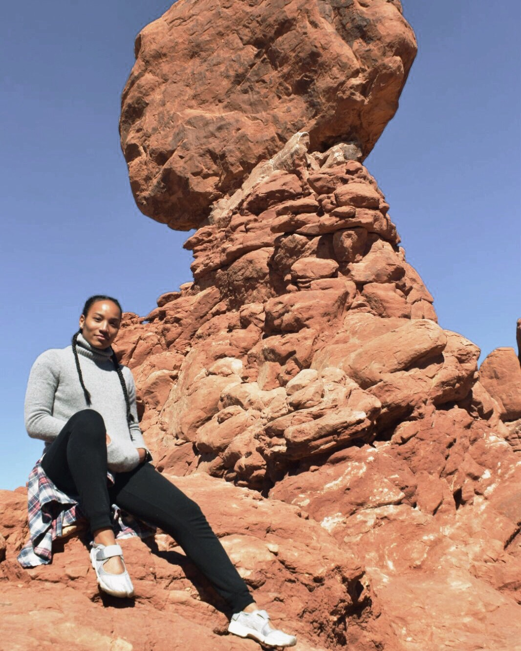 Illustrated by Sade - woman taking a photo in front of Balancing Rock in Arches National Park, Utah