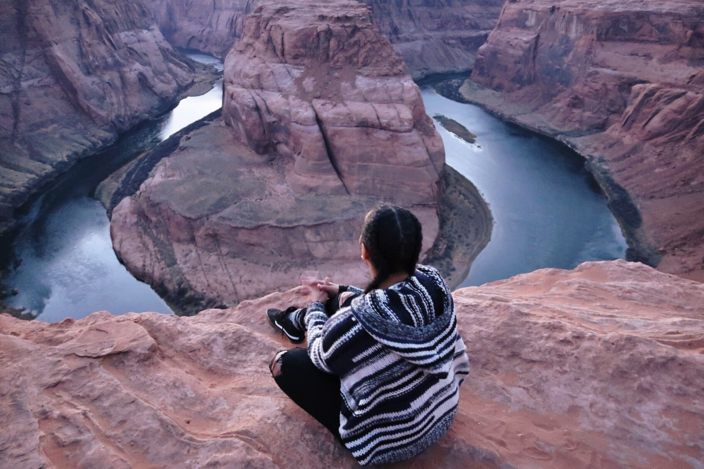 Illustrated by Sade - Woman sitting at the edge of the Colorado River's Horseshoe bend in Page, AZ