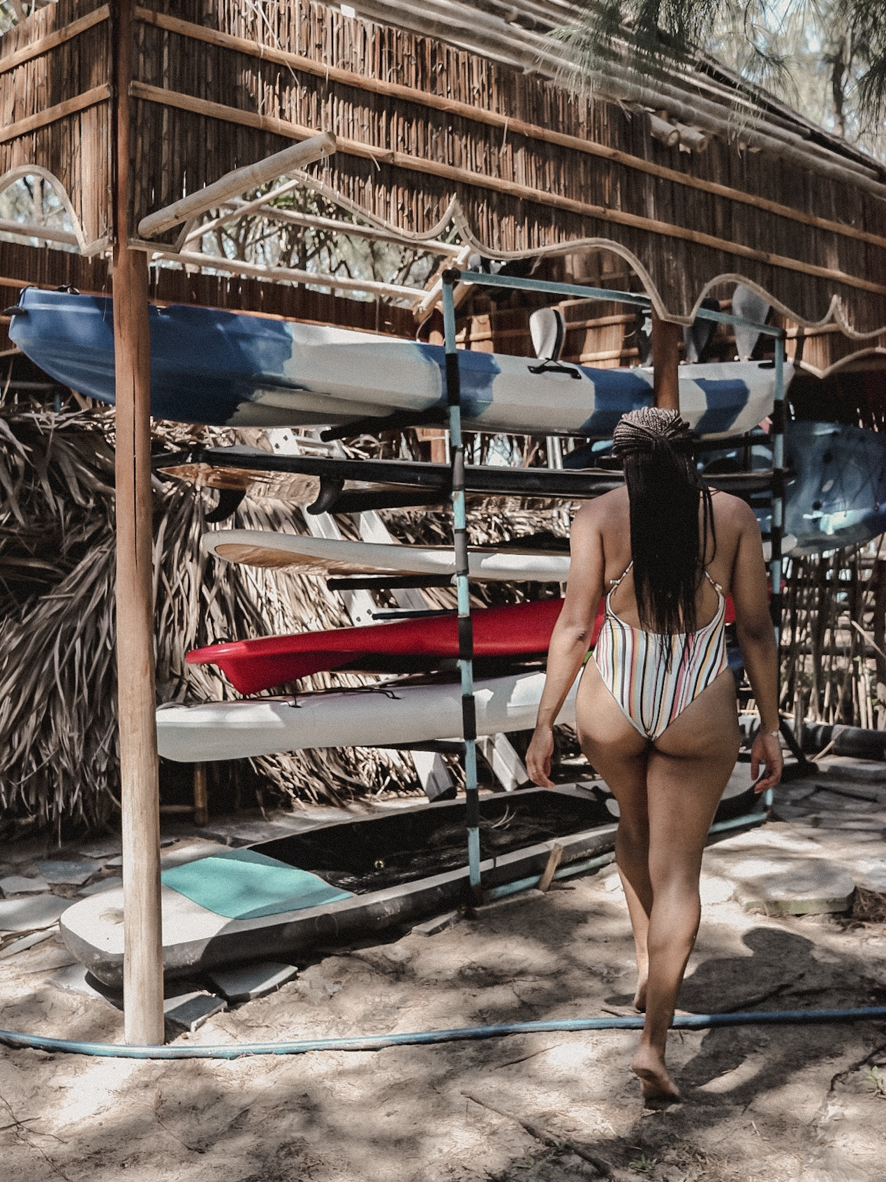 One-piece swimsuit feature photo next to surfing rentals at Kahuna's Beach Club Bar & Grill at An Bang Beach, Hoi An, Vietnam
