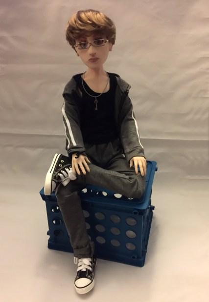 Simon seated cross legged on crate.