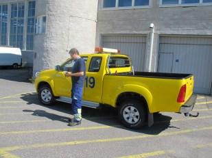 15.05. Keskiviikkopäivä oli kirkas ja lämmin. Keltaisen päivystyksen Hilux-avolavan kylkeen on maalattu iso numero 19. Auto erottuu hyvin ympäristöstä, kuten kuuluukin.