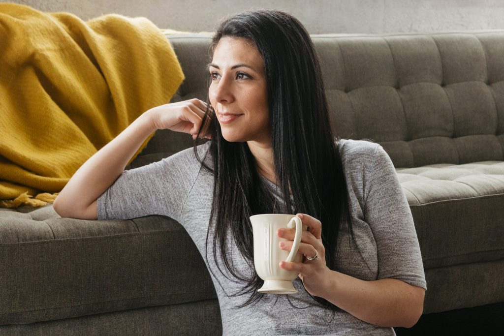 a woman sat with coffee at the foot of a sofa