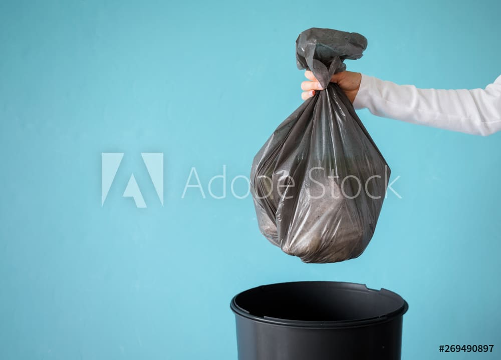 Hand holding garbage in plastic bag