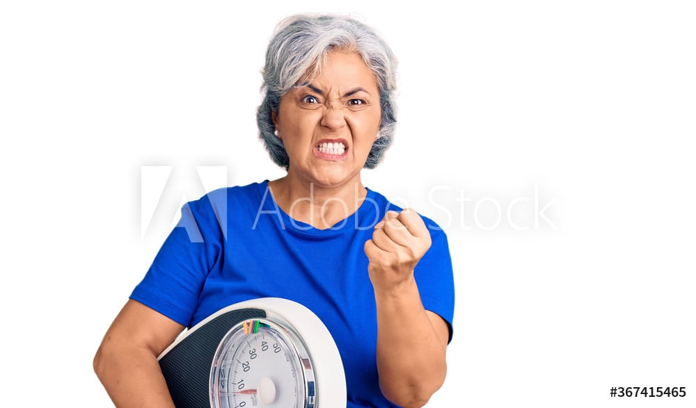 Senior woman with gray hair holding weight machine to balance weight loss annoyed and frustrated shouting with anger, yelling crazy with anger and hand raised