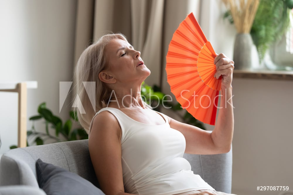 Stressed old woman waving fan suffer from overheating at home
