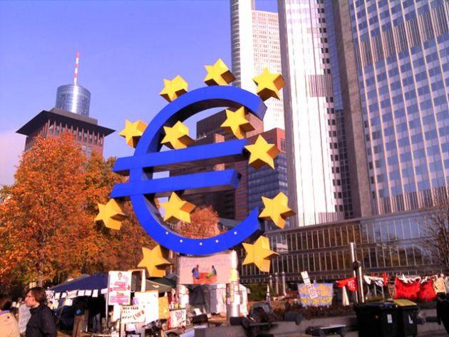 Il simbolo dell'Euro sotto la sede della BCE a Francoforte. Foto © ArcCan/ Wikimedia Commons / CC BY-SA 3.0 / remixed by Il Mitte
