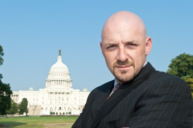 A man, arms crossed, looks into the camera. In the background is a capital building.