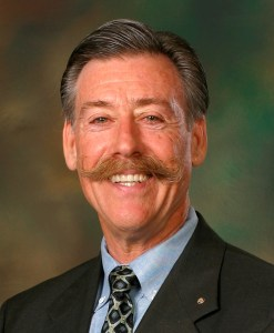 Photo of John Heveron, a smiling man in a suit and tie, with auburn hair and mustache with a little gray.
