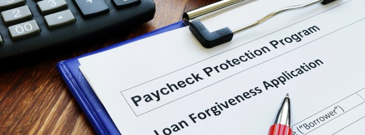 "CLipboard and pen with paper titled ""Paycheck protection loan forgiveness."