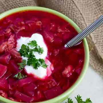 Red beet soup topped with parsley served in a bowl.