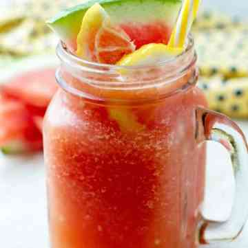 Blended watermelon in a large glass with yellow straw and few pieces of watermelon wedges behind it.