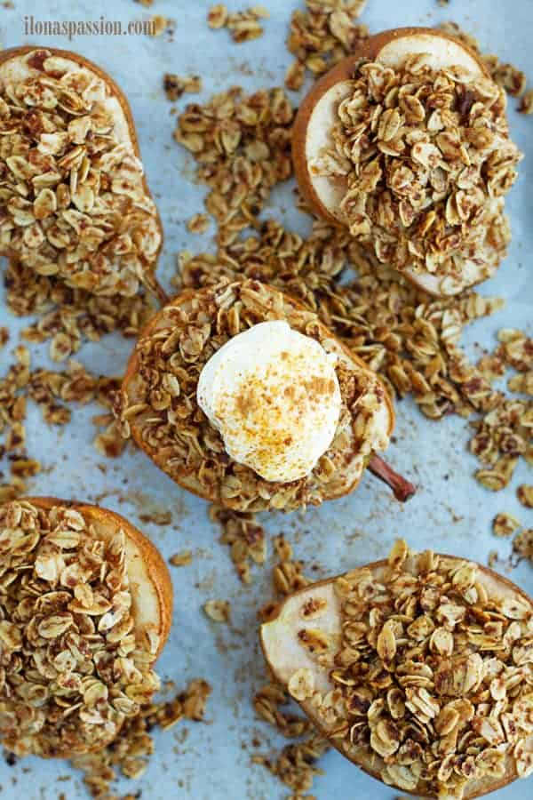 Granola stuffed roasted pear placed on baking sheet with parchment paper.