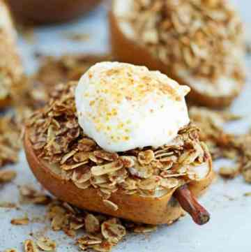 Healthy cinnamon sugar pear cut in half and topped with rolled oats.