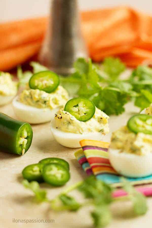 Spicy deviled eggs with cilantro, mayonnaise and jalapeno.