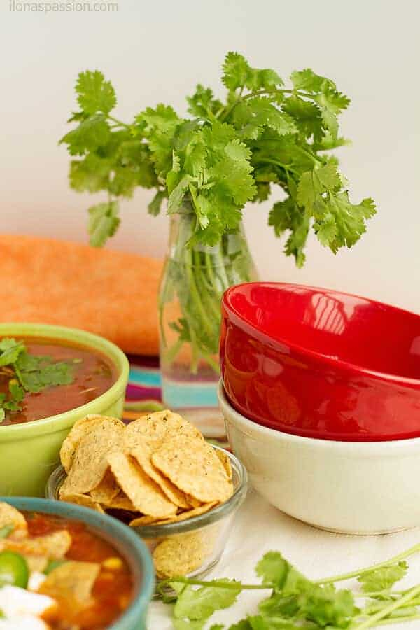Fresh herb cilantro in a bottle, few empty bowls and tortilla chips prepared for party.