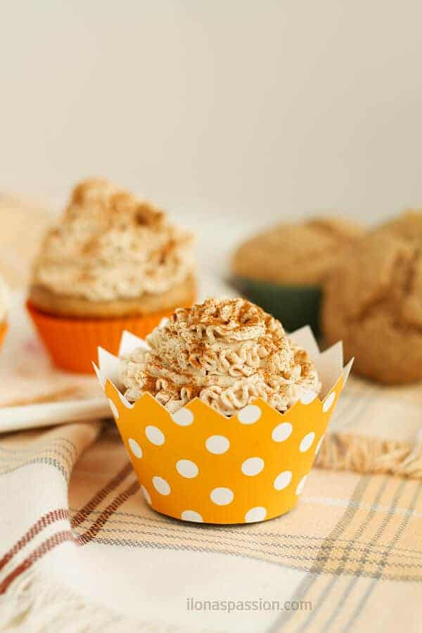 Cinnamon cupcake decorated in orange polka dot printable wrapper in front and few cupcakes in the back.