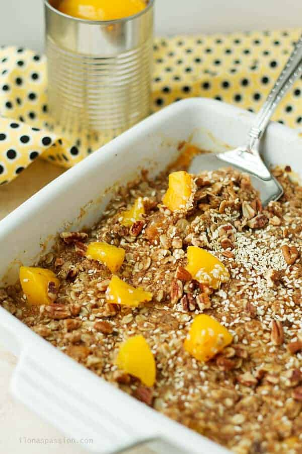 A spoon dipped in peach crumble made with coconut sugar, oats and sesame seeds. Canned peaches in the back.