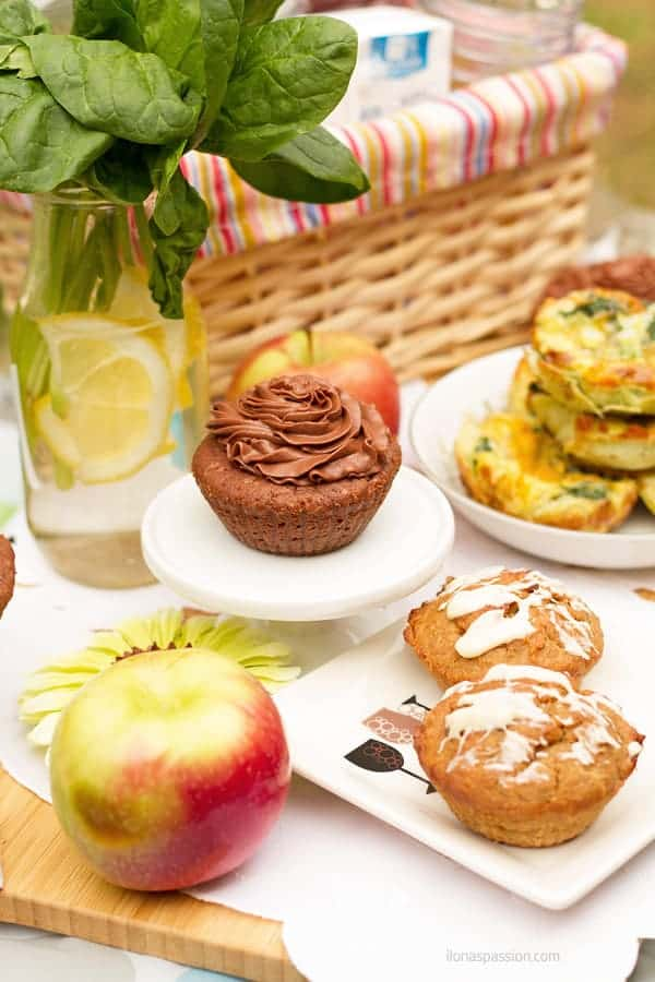 Brownies, apples, gluten free muffins, breakfast muffins on a table in the park.