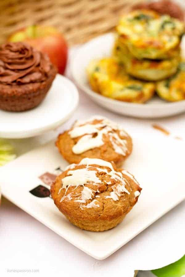 Banana muffins on a plate with chocolate cake in the back.