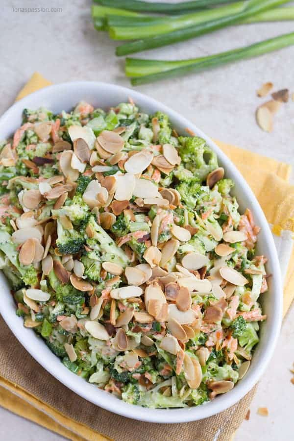 Vegetarian cold broccoli salad with shredded carrots and green onion.