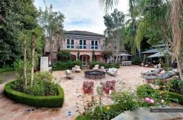 O pátio dos fundos da mansão é amplo e com grande área verde