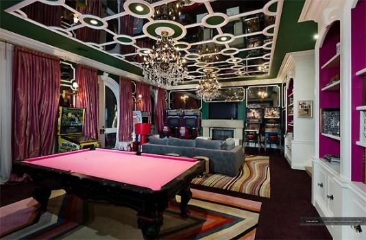 A sala de jogos tem teto espelhado e uma mesa de cinuca rosa