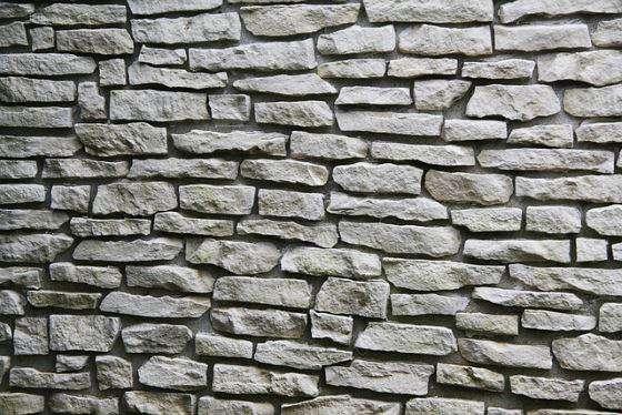 Parete in pietra finta o vera in soggiorno camera da letto con faretti esempi