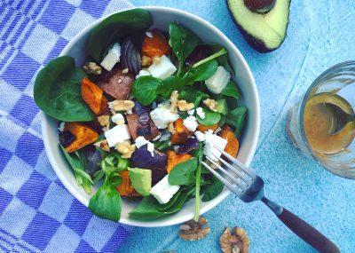 Lauwwarme lunch salade van gegrilde zoete aardappel en rode ui met feta, avocado, spinazie, veldsla, walnoten en een dressing met citroen en rauwe honing. Smullen, makkelijk en passend in je detoxkuur.