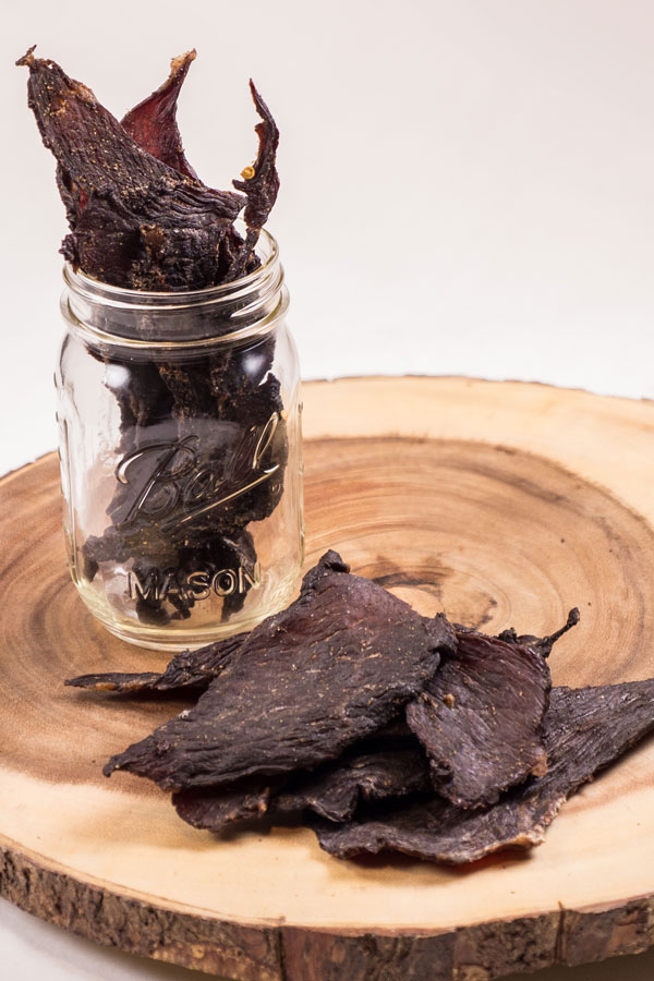 Beef Jerky laying on a piece of wood and inside a mason jar