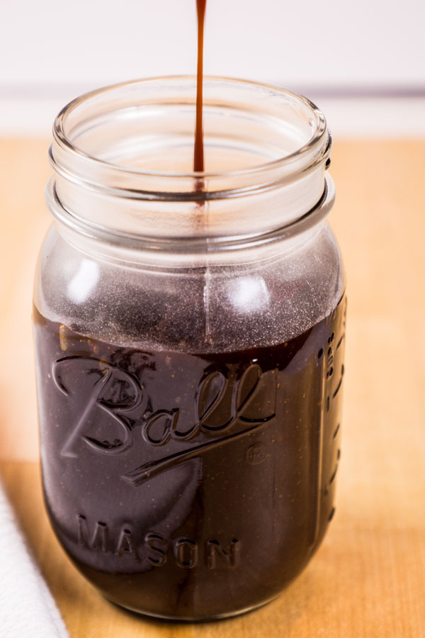 Sticky sweet bbq sauce being poured into a mason jar.