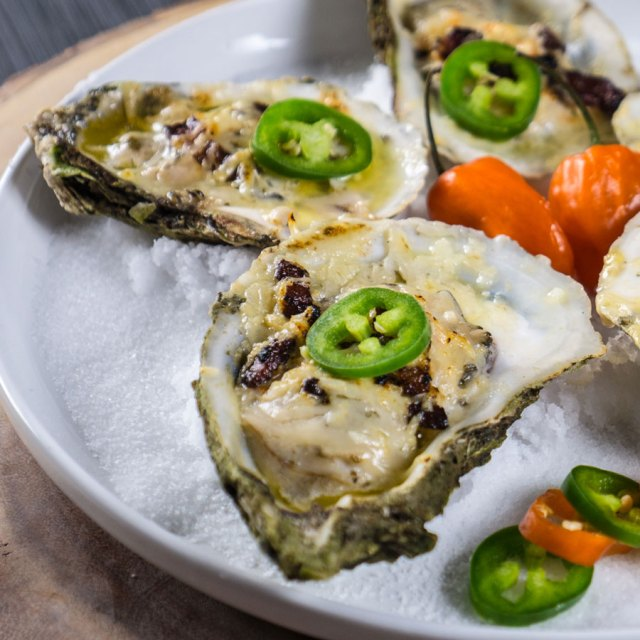 Spicy grilled oysters sitting on a plate of salt.