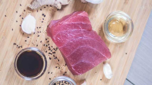 Raw tuna steak with toasted sesame seeds on a cutting board.