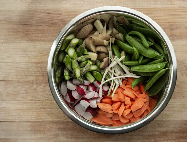 Diced Spring vegetables in a stainless steel bowl