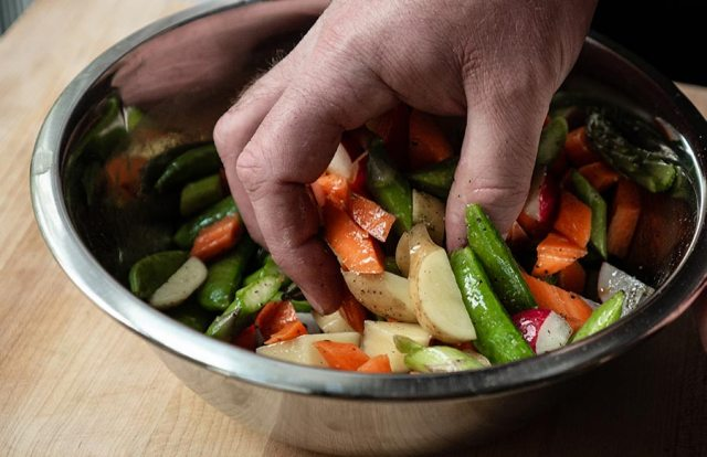 A hand mixes diced spring vegetables and olive oil in a bowl.