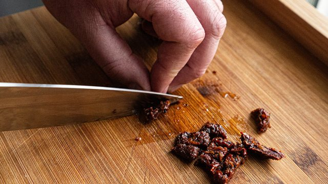 Sun-dried tomatoes being roughly chopped